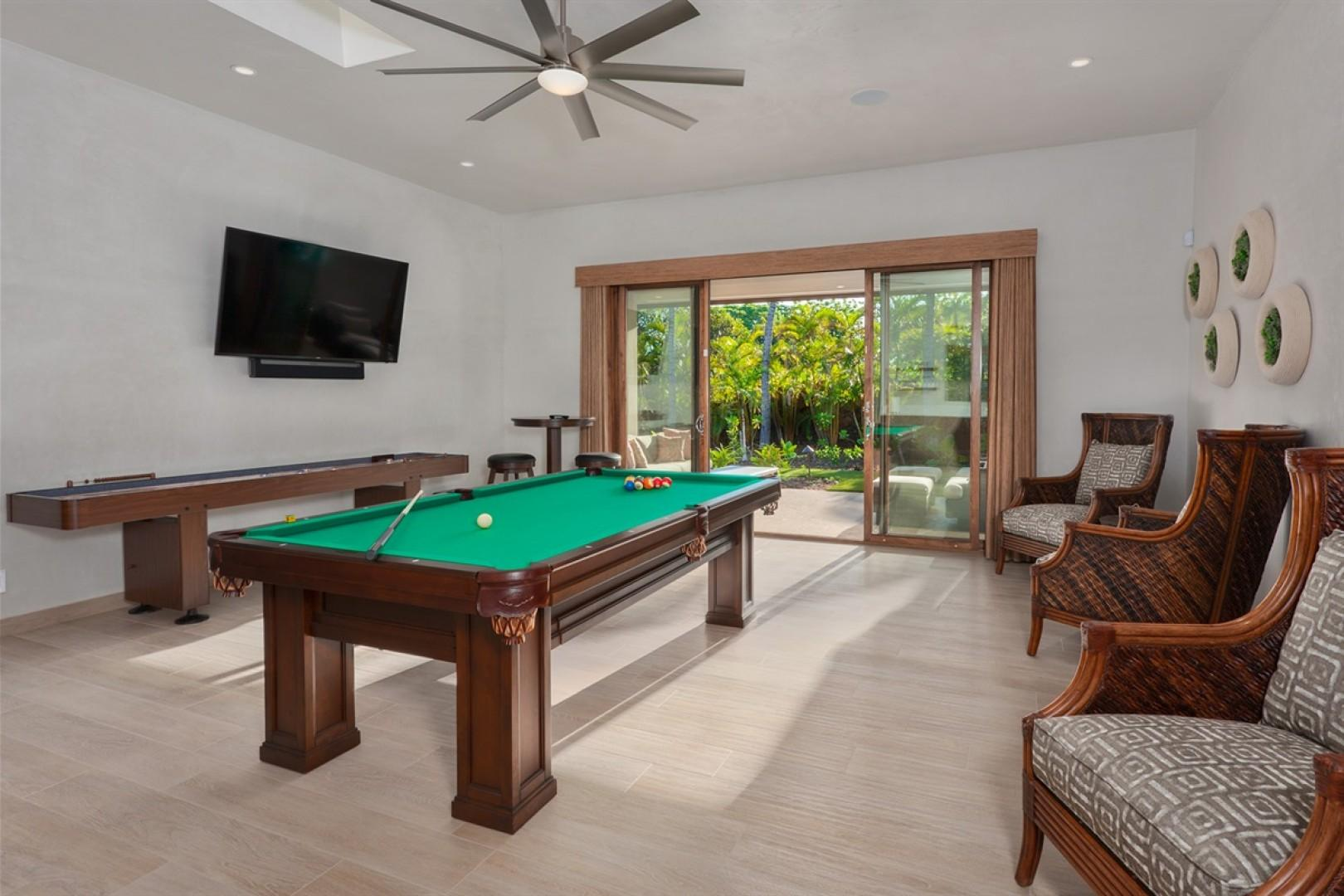 """Game room equipped with pool table, shuffleboard, wet bar and 65"""" Smart flat screen television."""