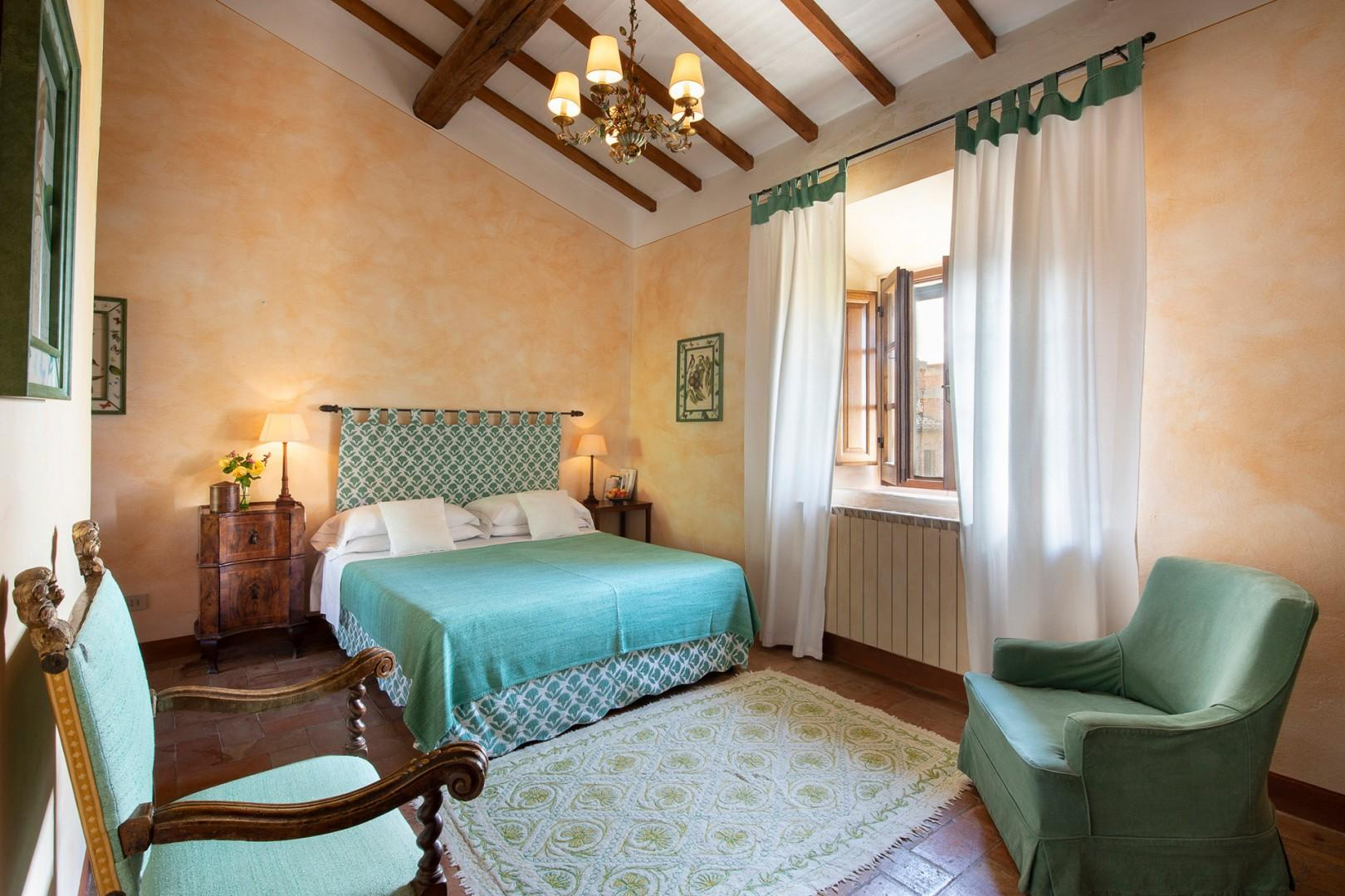 High beamed ceiling in bedroom 1 with windows overlooking the garden and orchards.