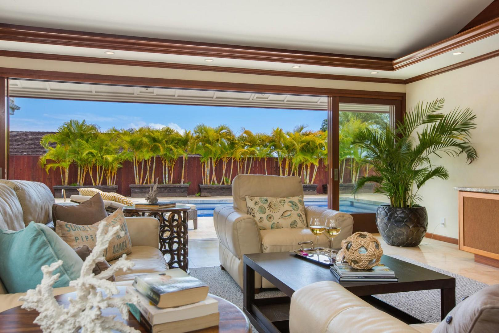 The open living room floor plan with vaulted ceilings flows seamlessly to the outdoors with a 16-foot-tall cherry wood door system that lets the gentle Hawaiian breeze sweep through.