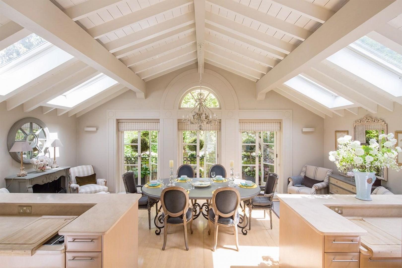 Spacious dining room and kitchen with large windows overlooking the vibrant terrace
