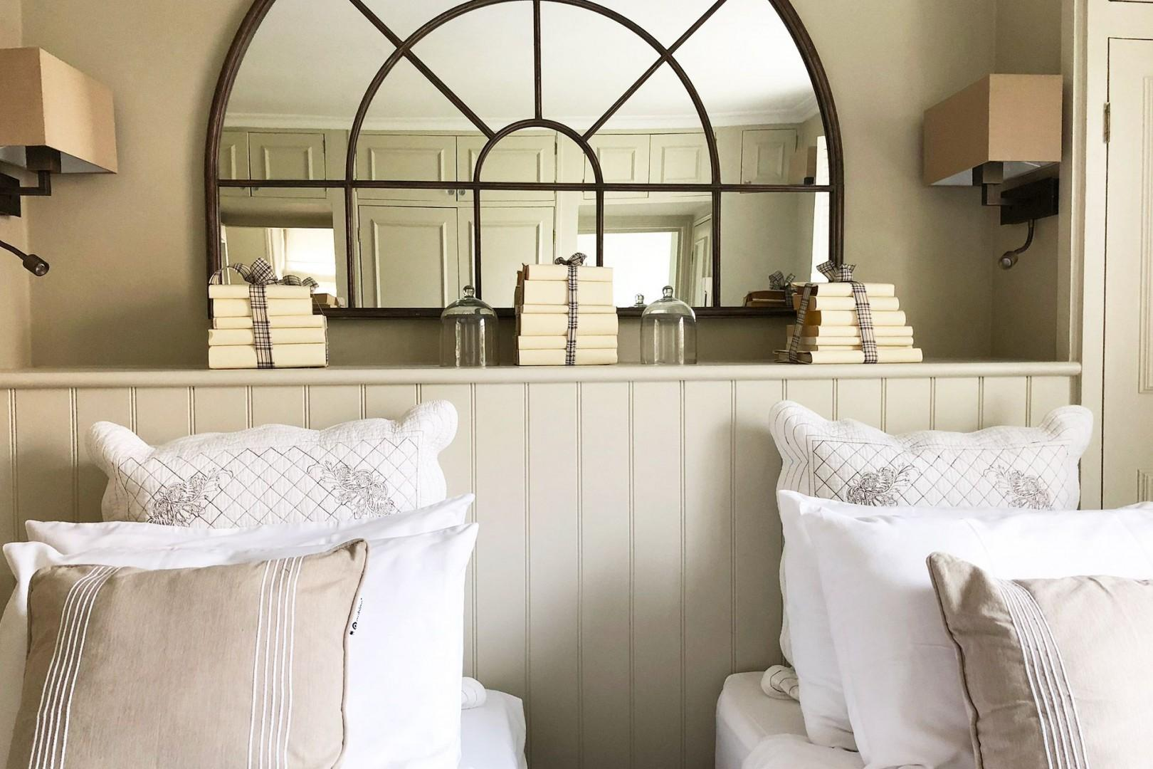 Shelf and window frame mirror above the beds