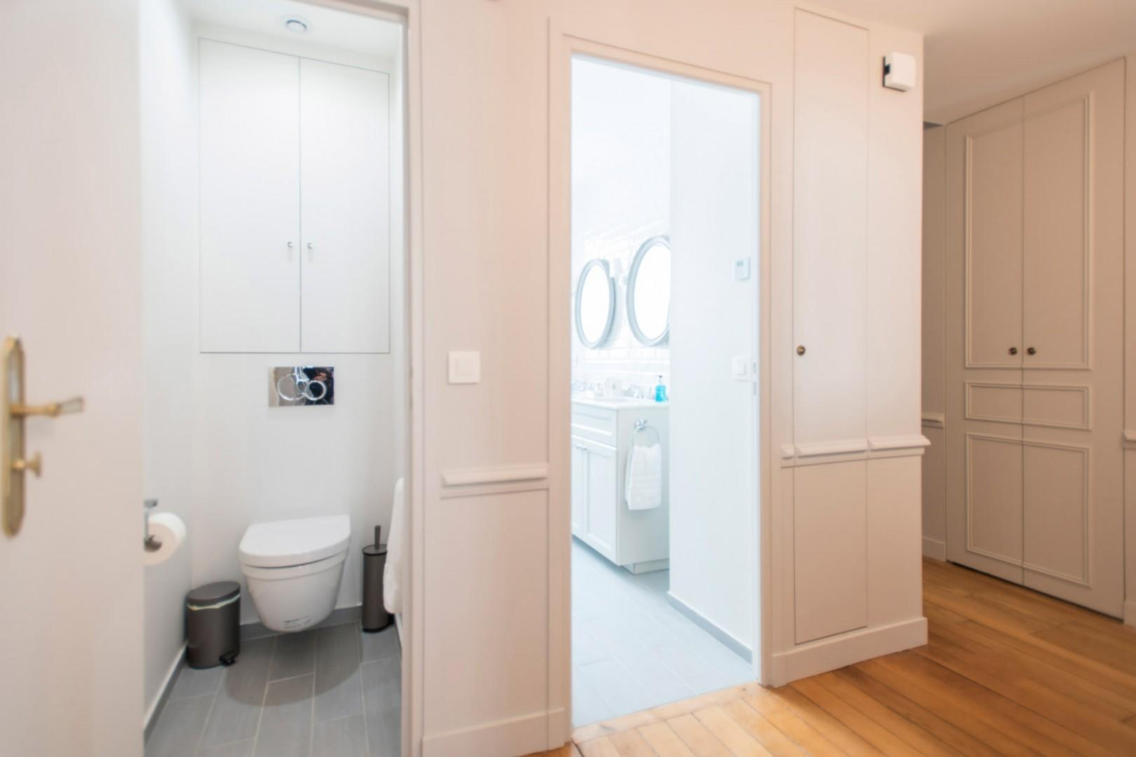 There is a practical half bath with toilet and sink next to bathroom 1.