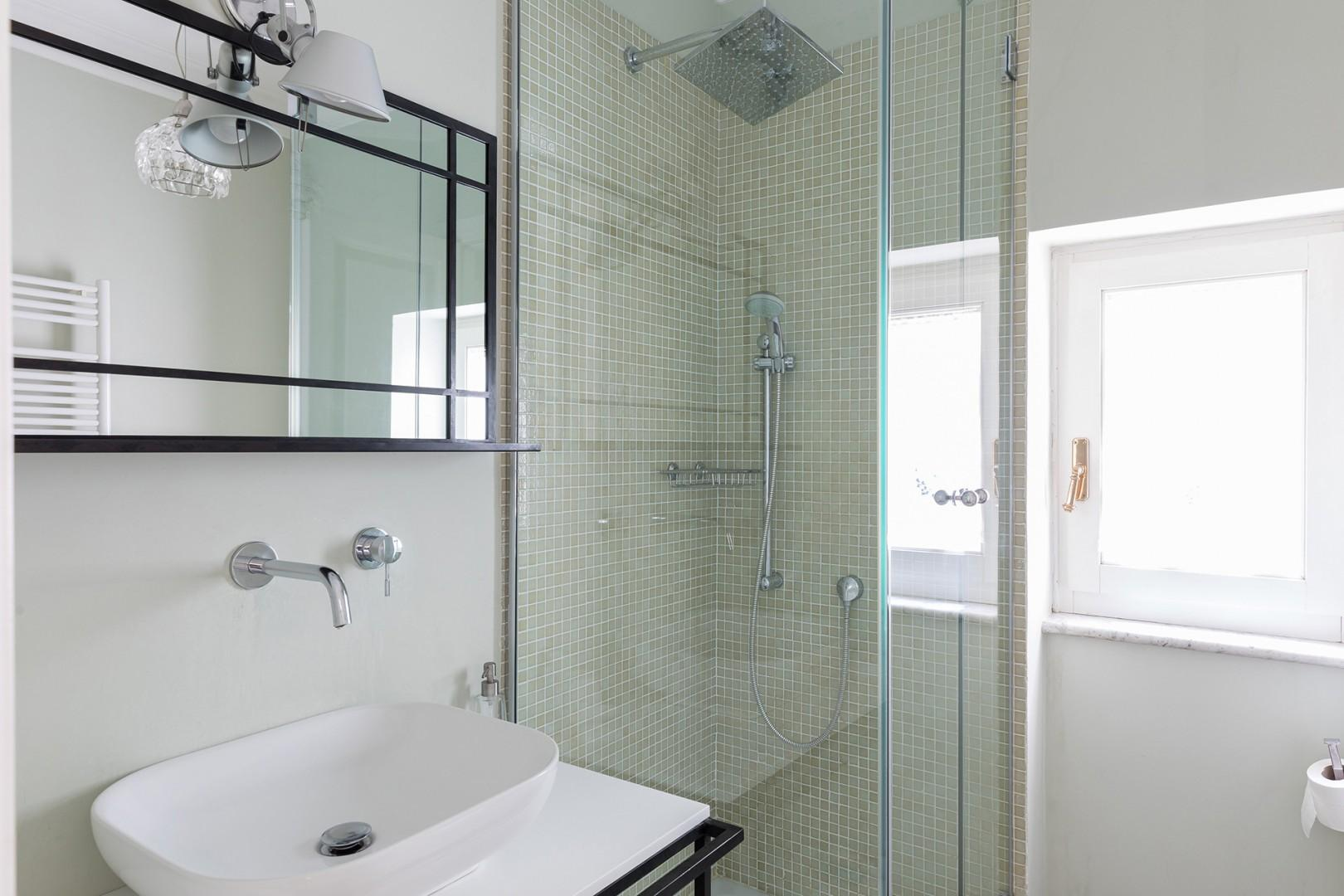 Bathroom 3 across the hall from bedroom 3 has a shower with both rainfall showerhead and handheld.