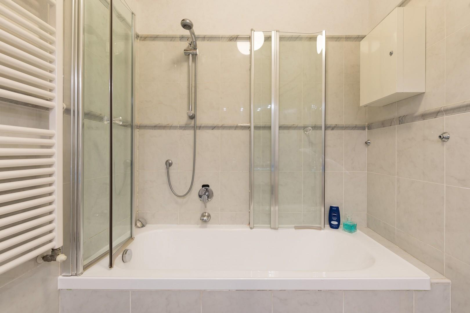 Ingenious shower enclosure which folds back flush to the wall, out of the way when taking a bath.