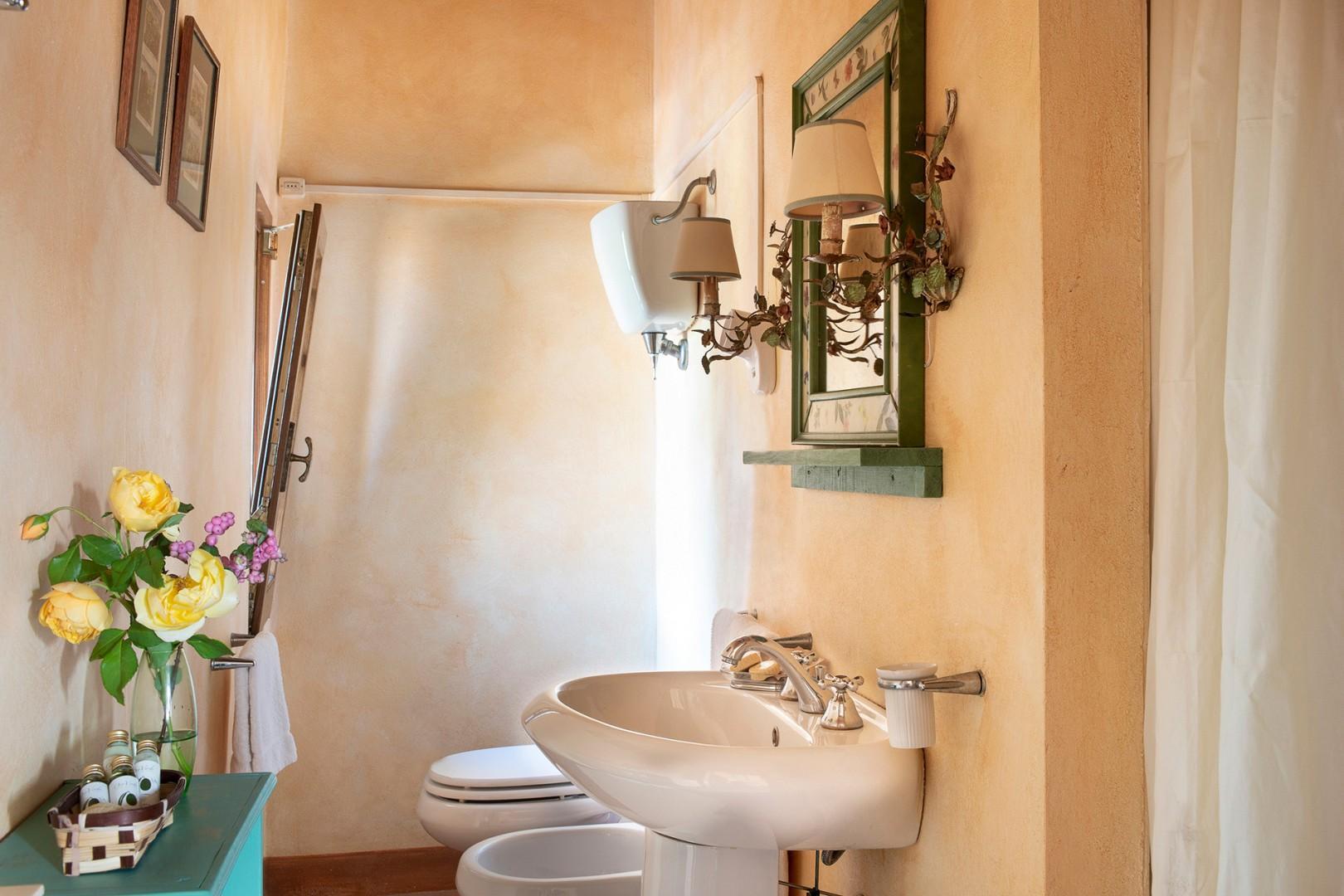 En suite bathroom has a shower, sink, toilet,  bidet, and nice courtyard view.