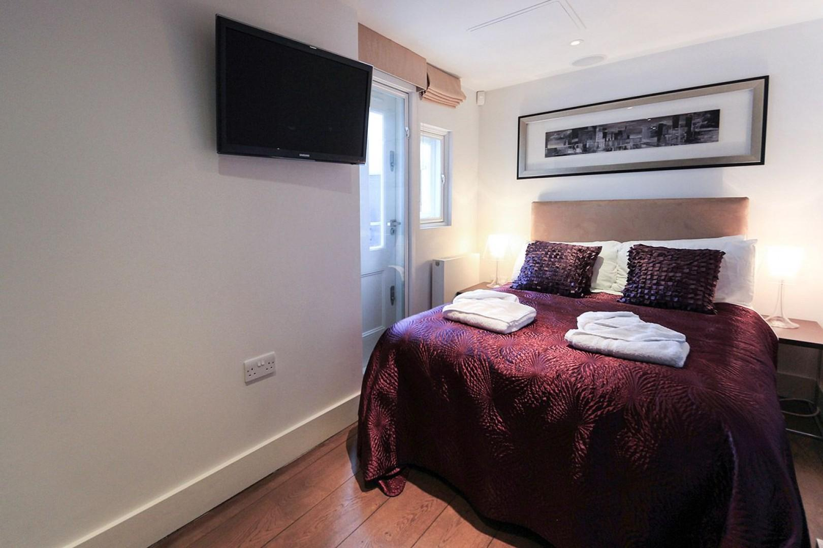Second bedroom with a comfortable bed and flat screen television