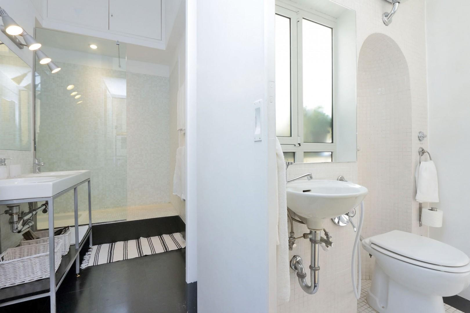 Bathroom 3 has double sinks and a large glassed-in shower. Accessed of the kitchen.