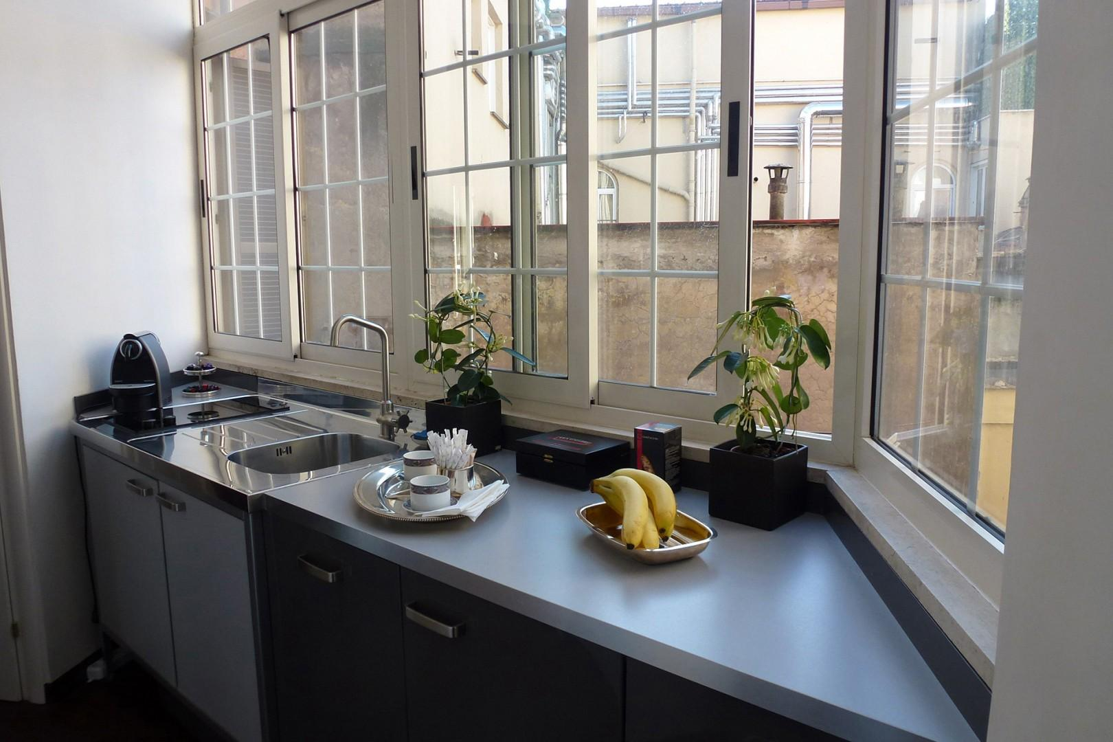 The kitchen has a wall of windows overlooking the courtyard and rooftops.