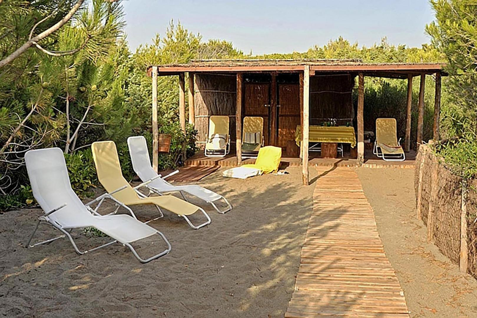 Private cabana with table, chairs, lounge chairs and a shower.