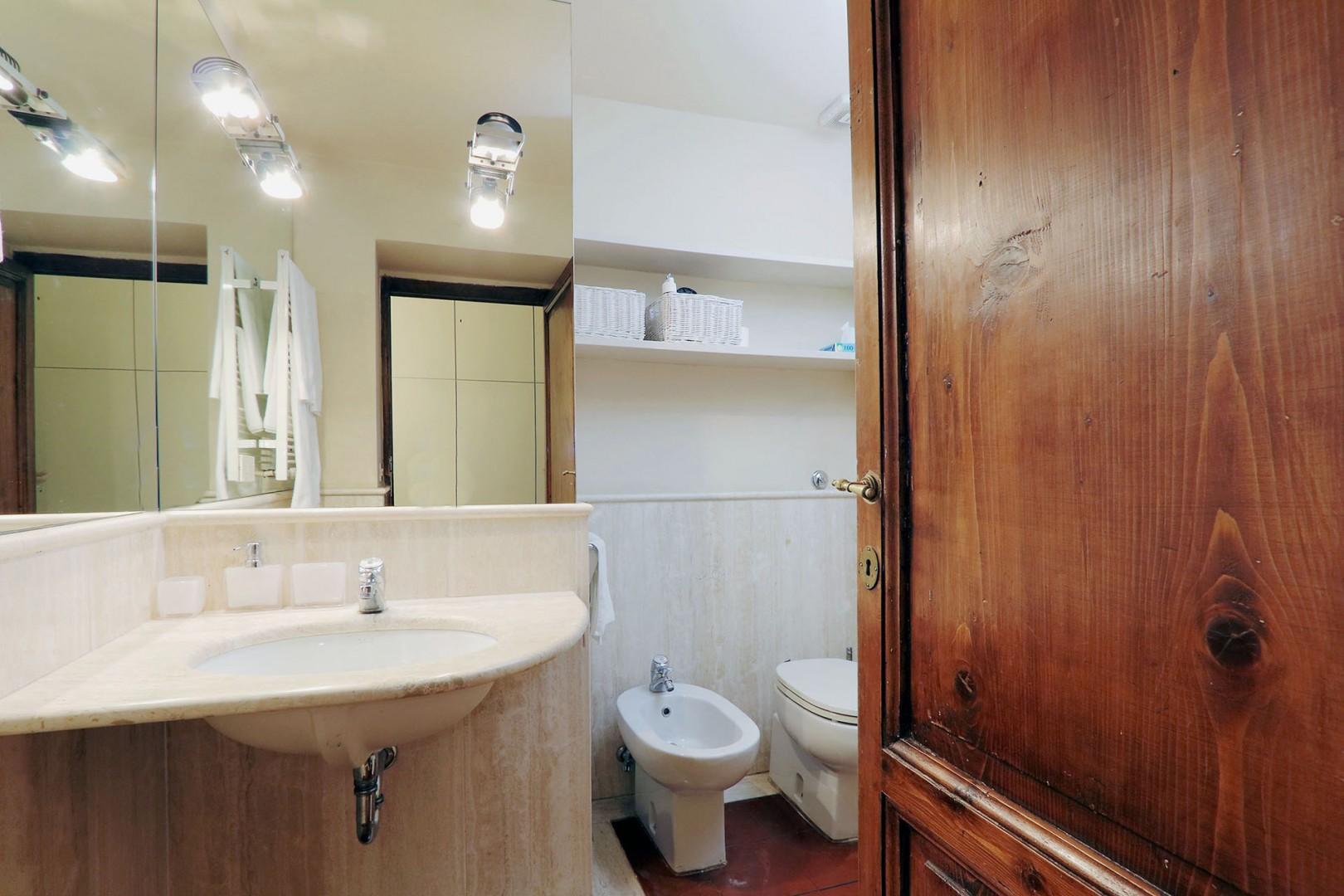 Off the hallway is bathroom 2. Marble walls, sink, toilet, bidet and shower.