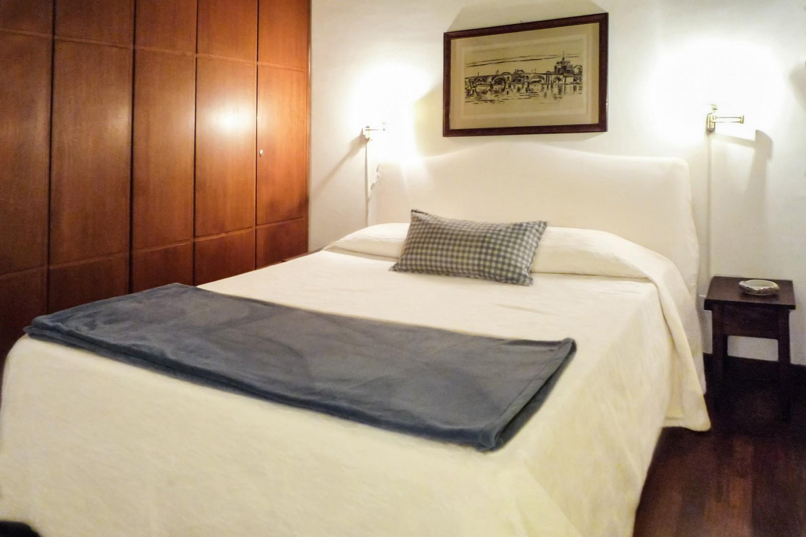 Comfortable bed with an etching of the Bridge of Angels over the Tiber river above it.