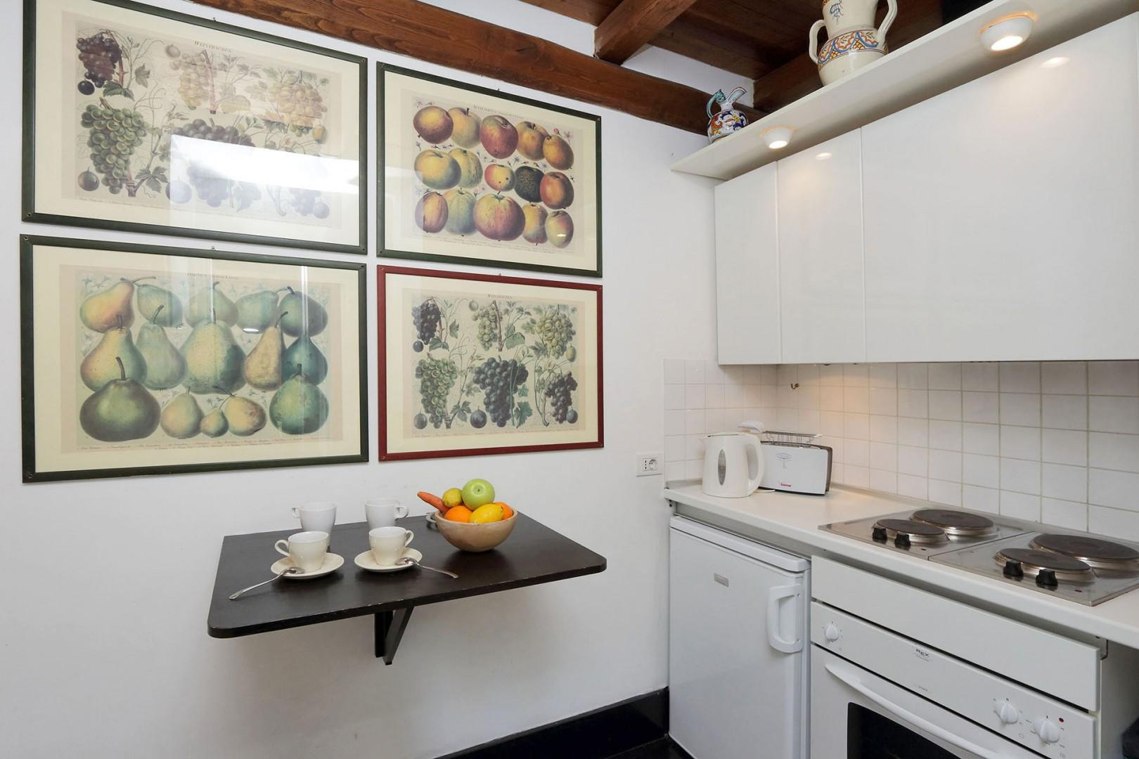 The well-lit, galley style kitchen has the sink and dishwasher with cabinets above on one side.