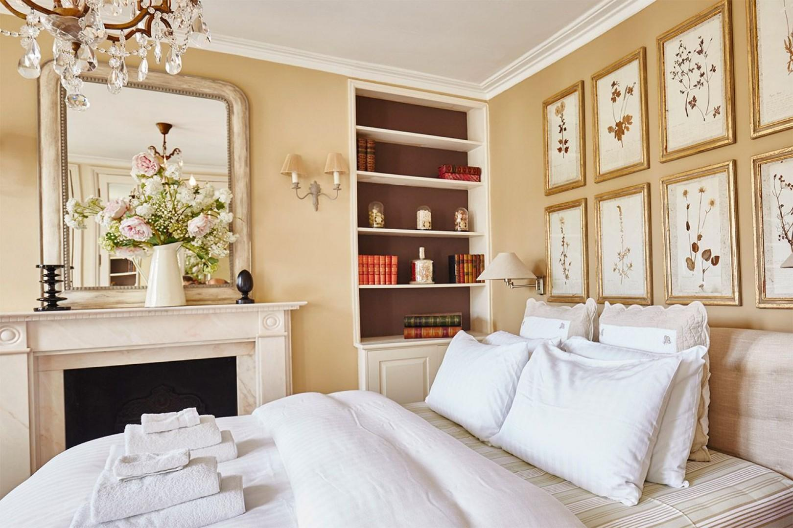 Marble fireplace and built in bookcase on one side of the first bedroom
