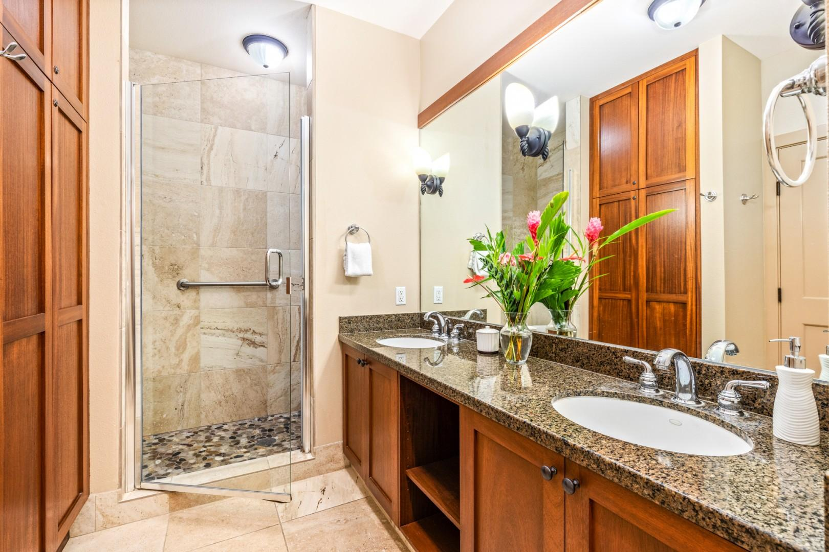 Master bath with dual sinks, walk-in shower, and W/C area with supportive grab bar handles.