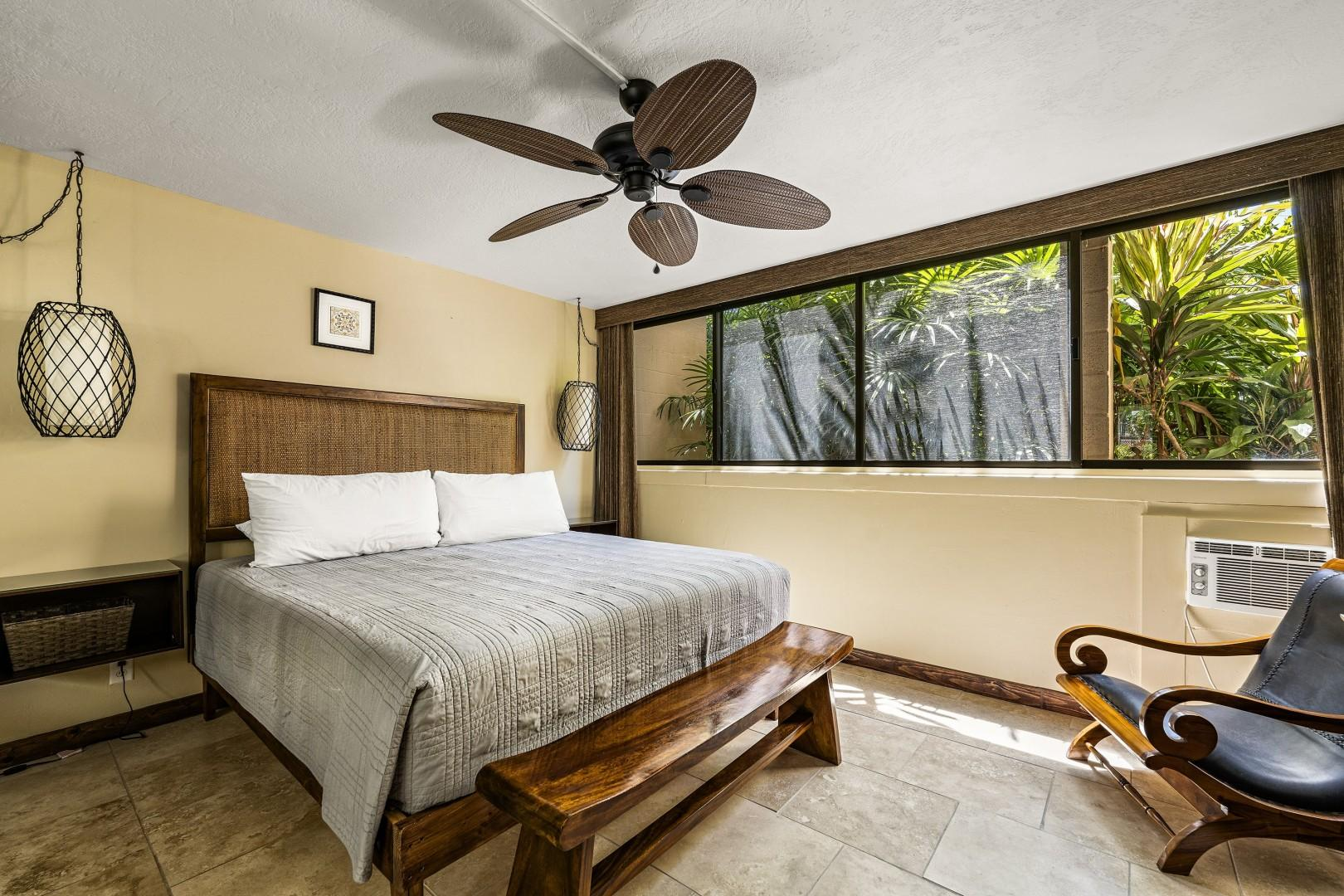 Luxurious King sized bed in the bedroom with green scape out the window