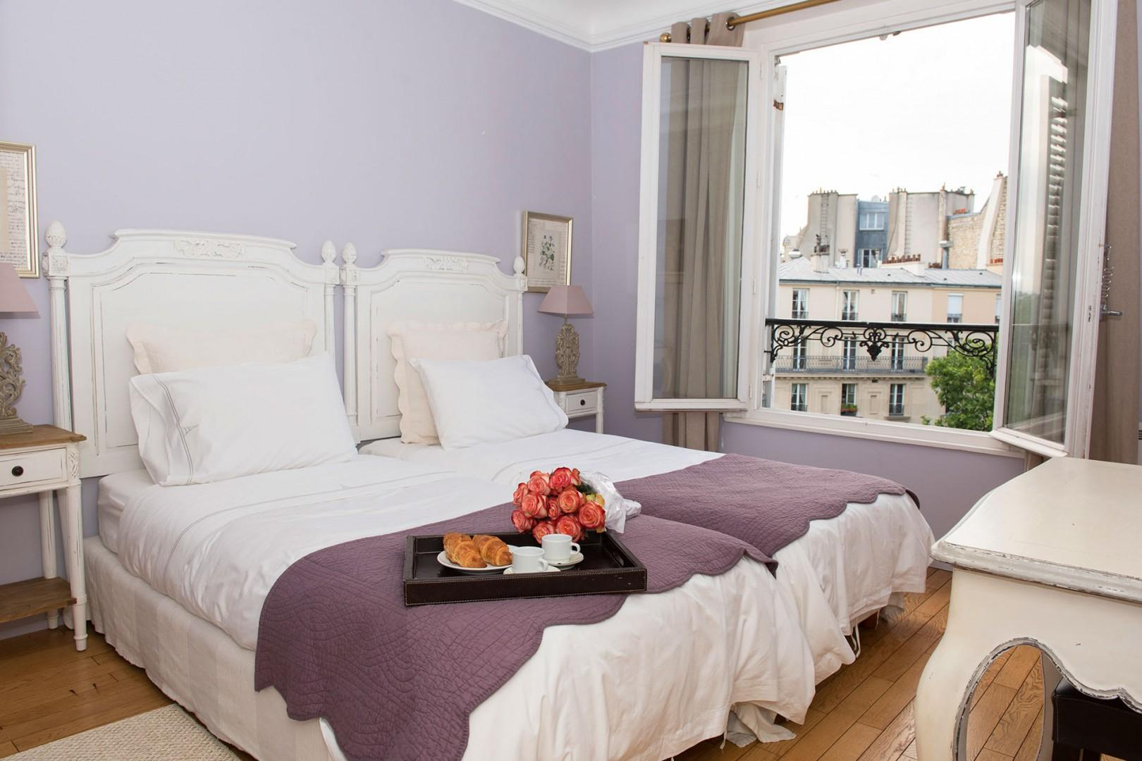Bedroom 2 has comfy beds and Eiffel Tower views.