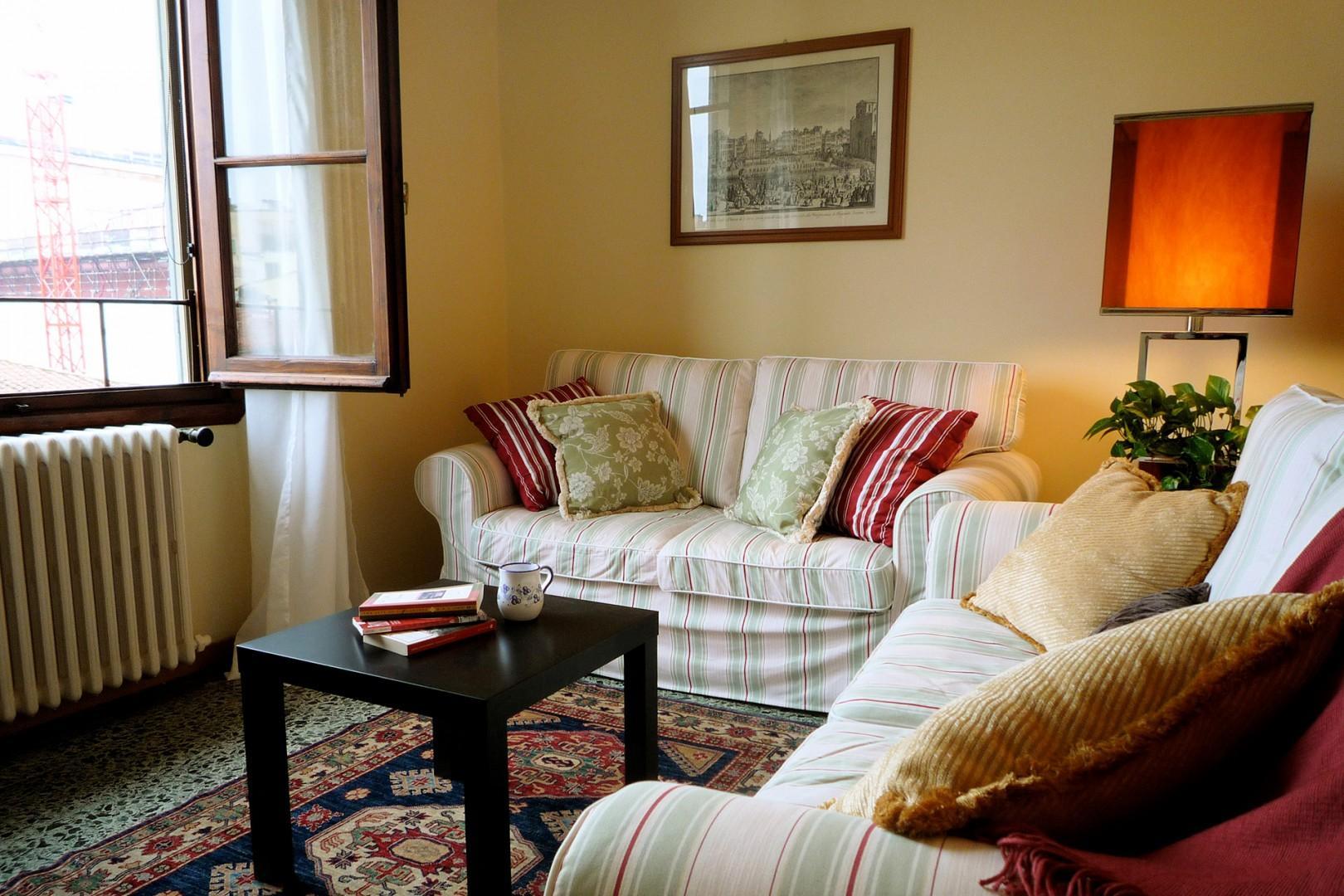 Large living room window admits lots of light. Original polished terrazzo floors.