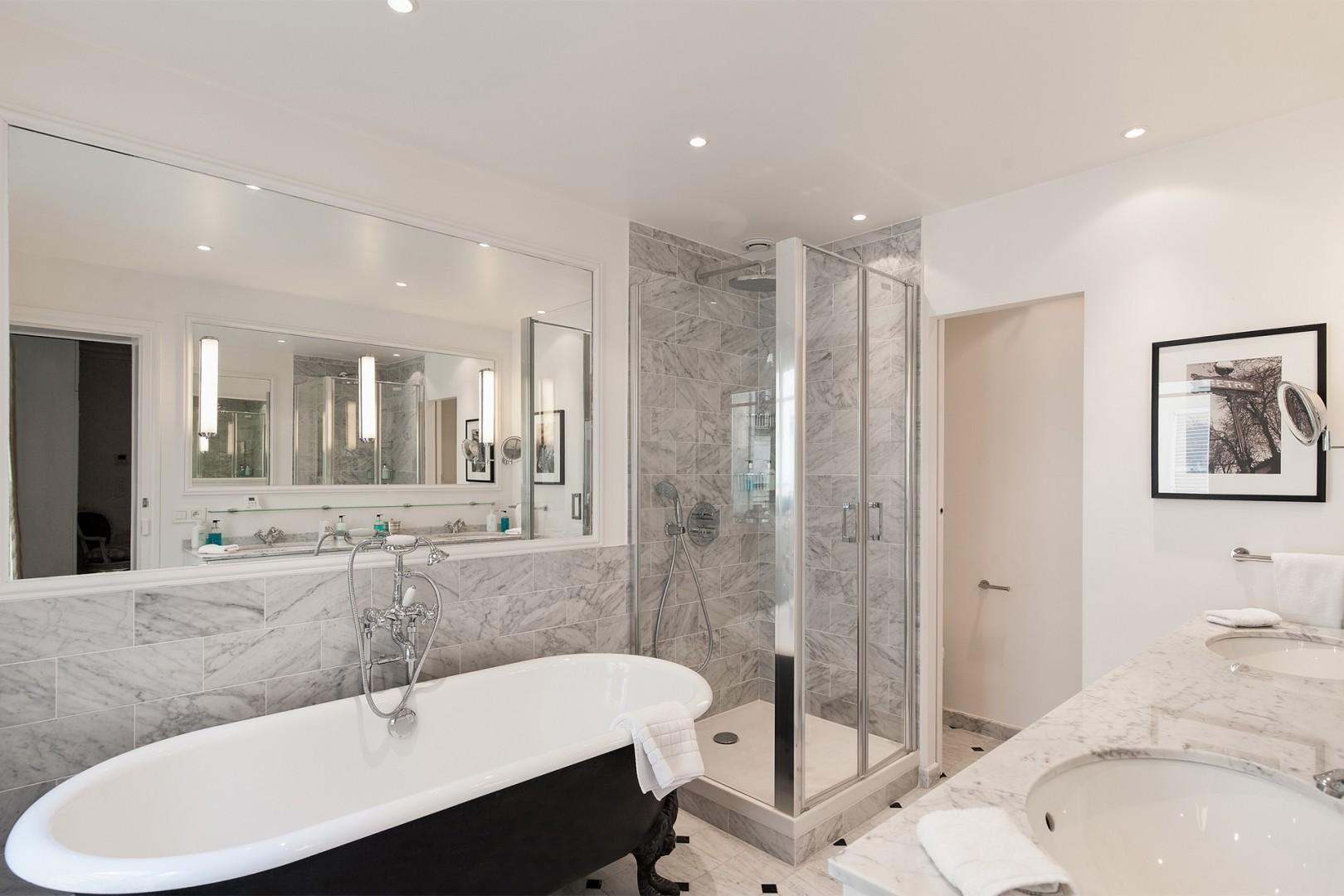 The en suite bathroom 1 is a glistening setting of gray marble.