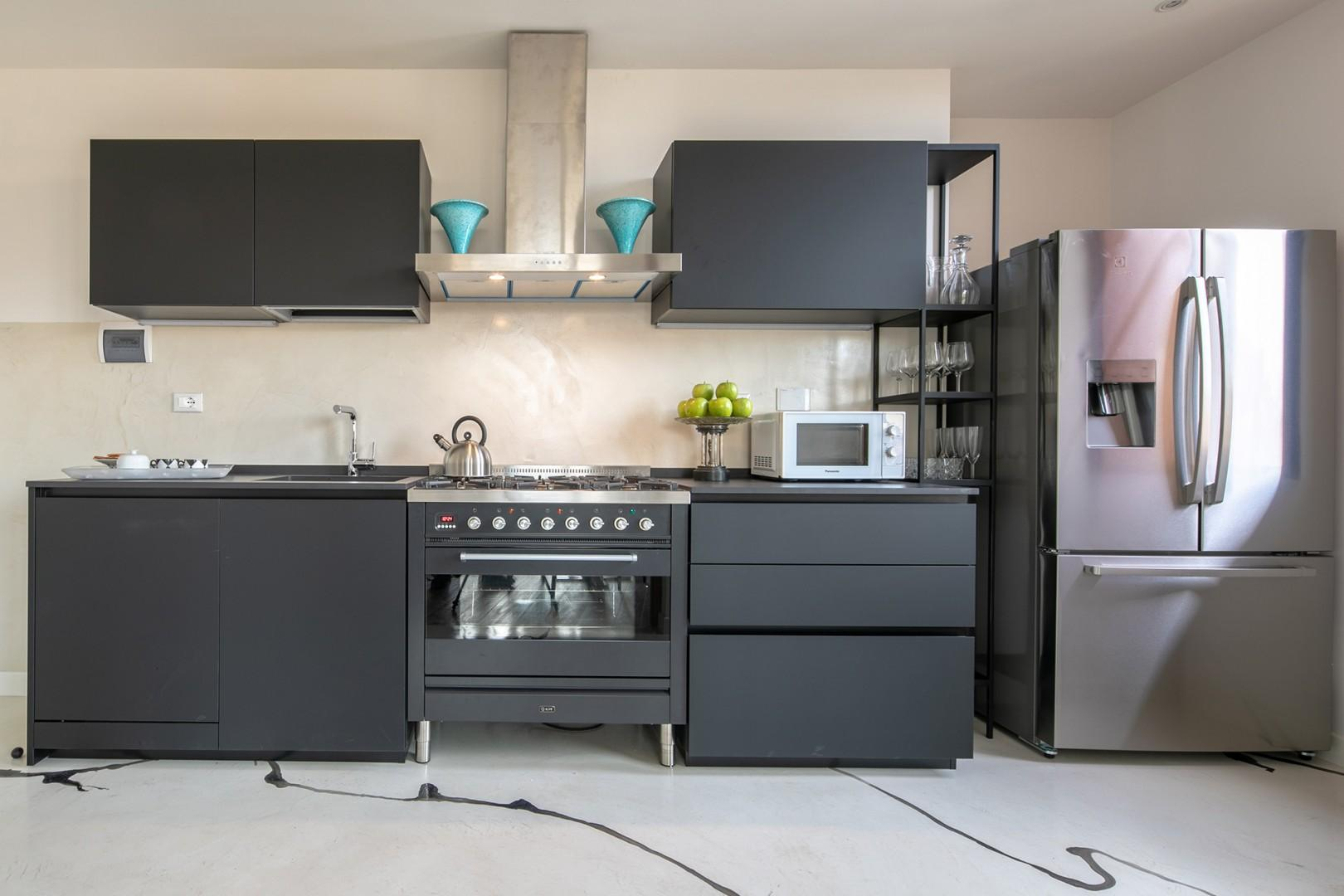 Bright modern kitchen with full-size refrigerator and six-burner stove.