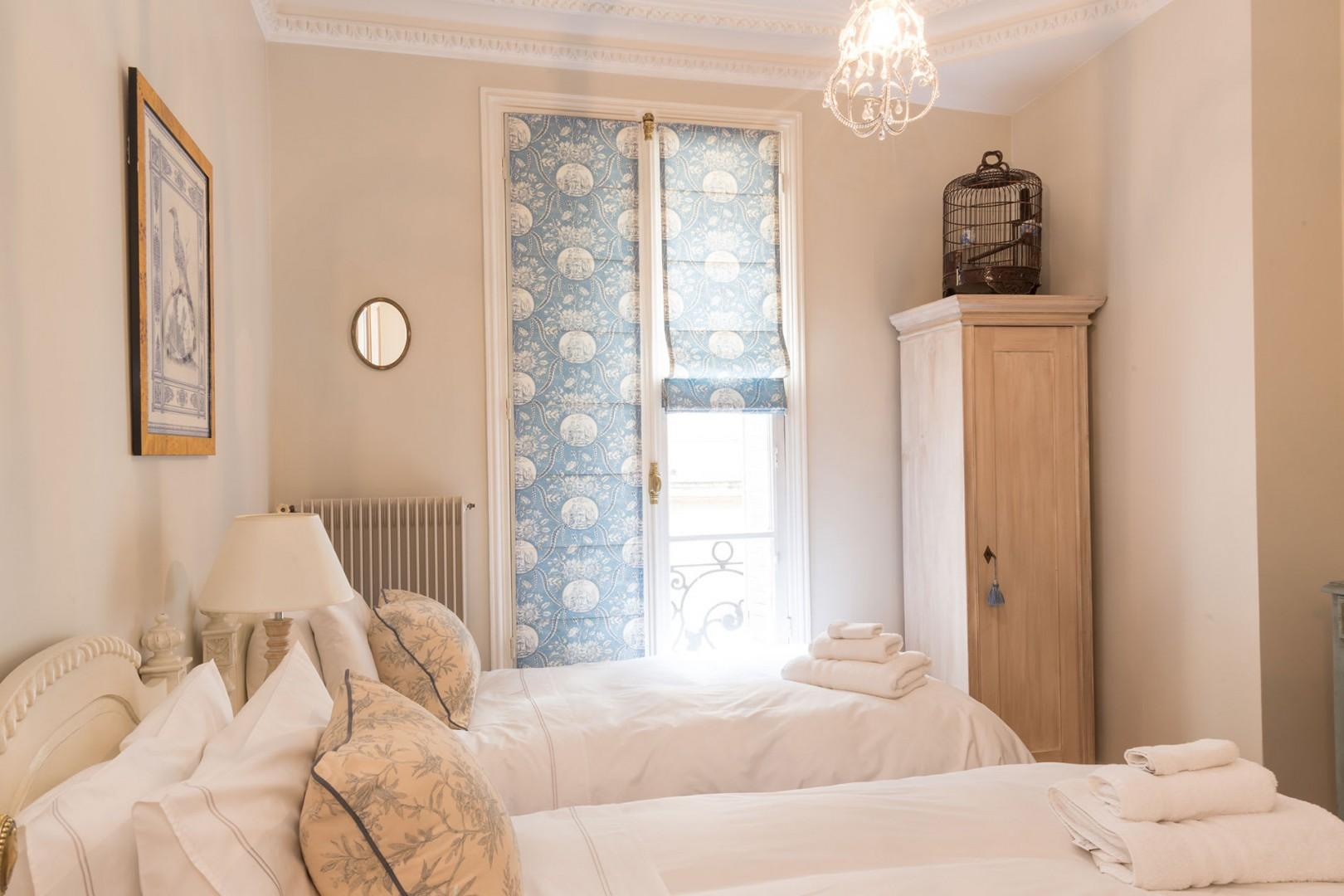 The charming bedroom 2 has lots of natural light.