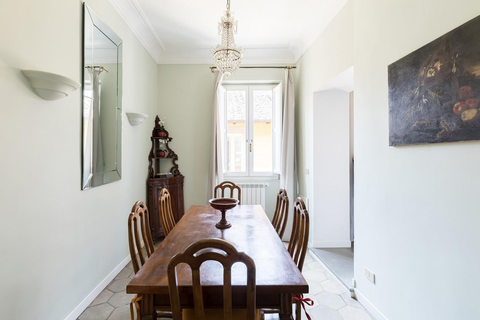 The dining room is separated from the living room, on the right, by a wall with two openings.