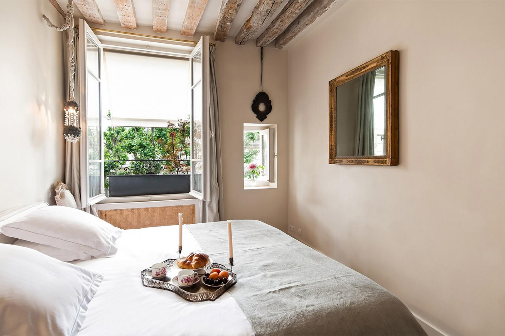 Wake up in the dreamy Paris bedroom with windows overlooking the street.
