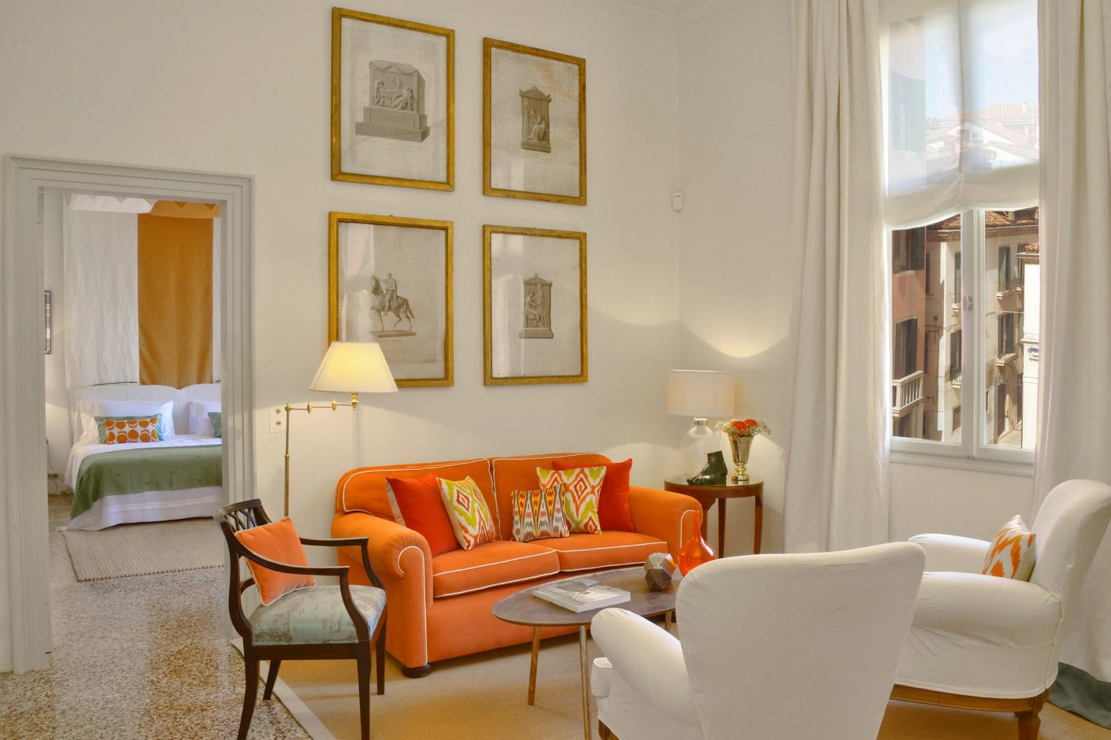 The bright living room of the Menta apartment with antique prints above the sofa.
