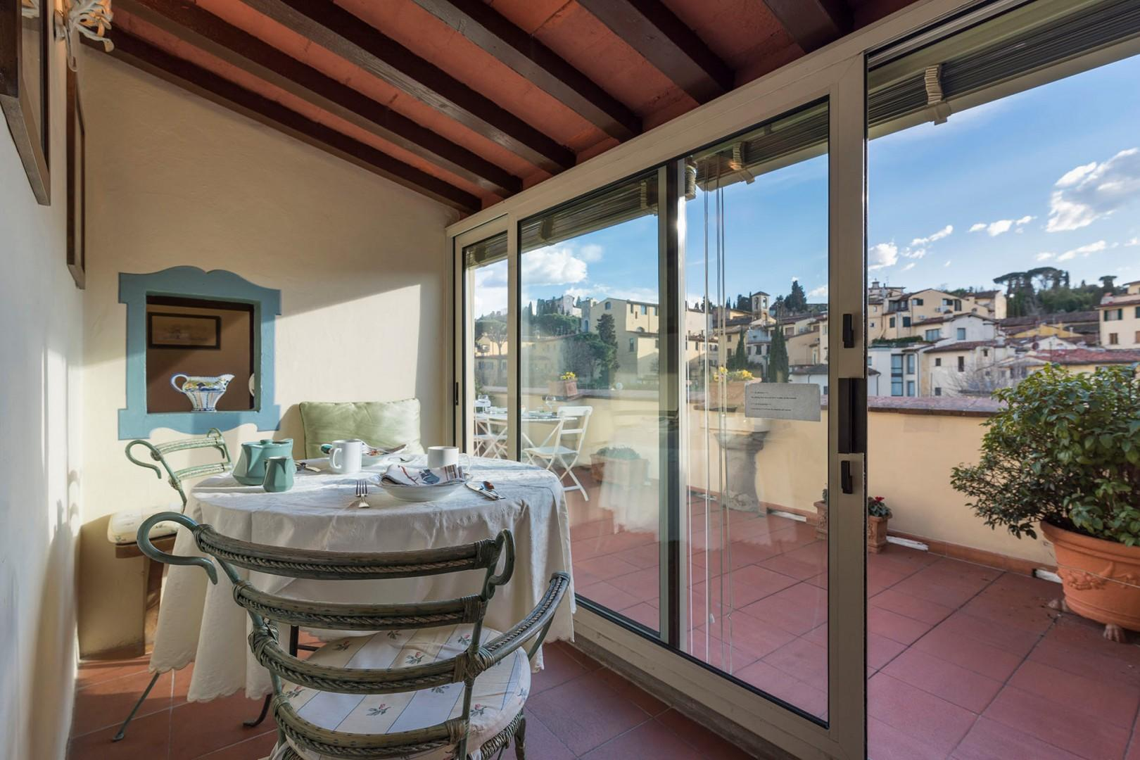 Glass enclosed sun room has a dining table with seating for 2 and views out the terrace.