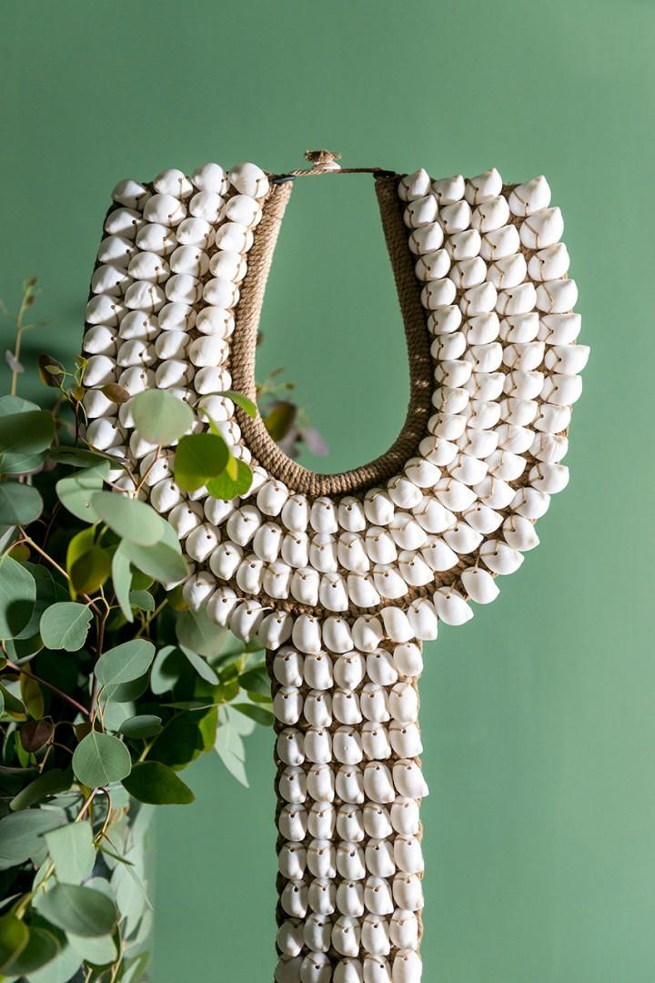The apartment boasts interesting artwork, such as this Papua New Guinea collar made from shells.