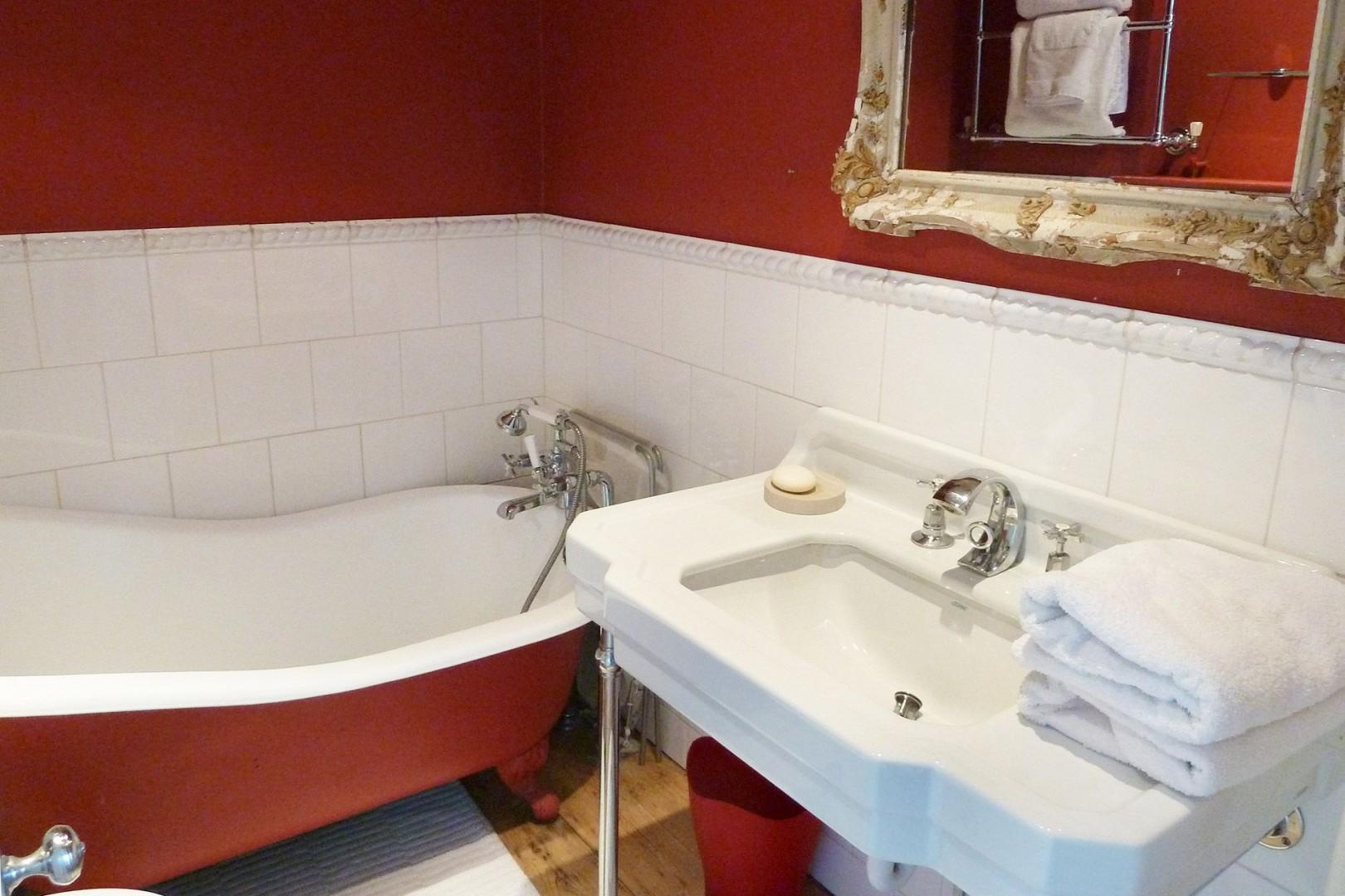 En suite bathroom to second bedroom with clawfoot cast iron bathtub