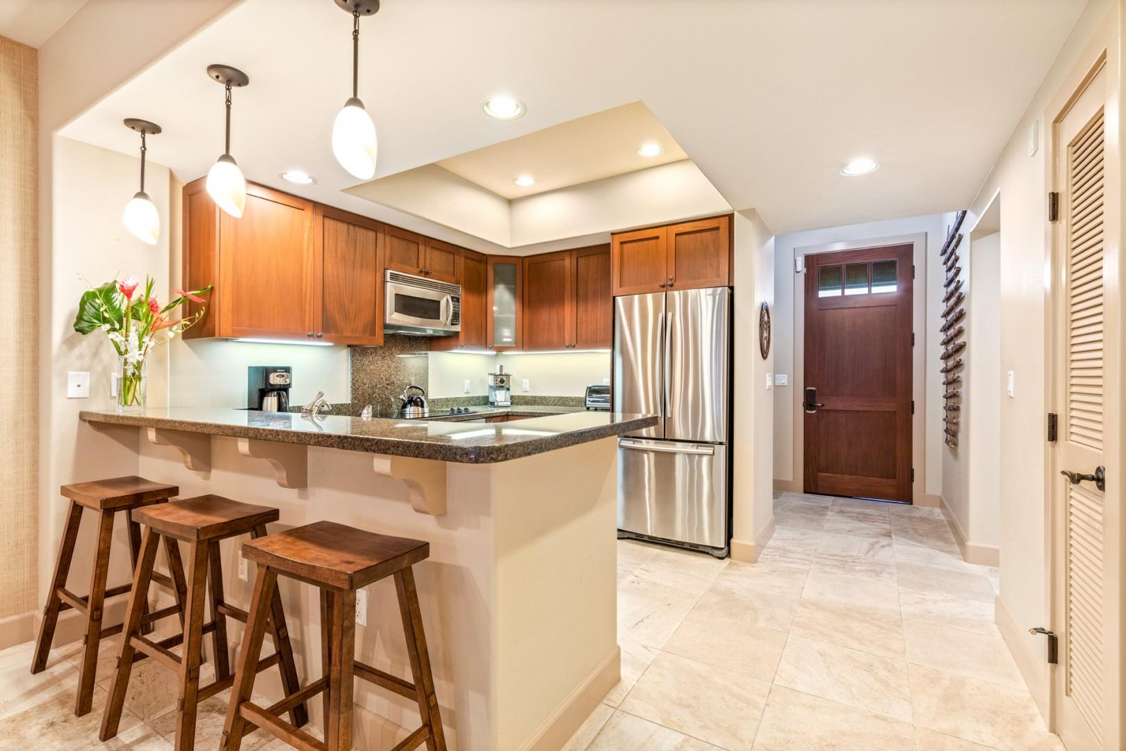 Wide view of open concept gourmet kitchen with granite countertops, stainless steel appliances and bar seating.