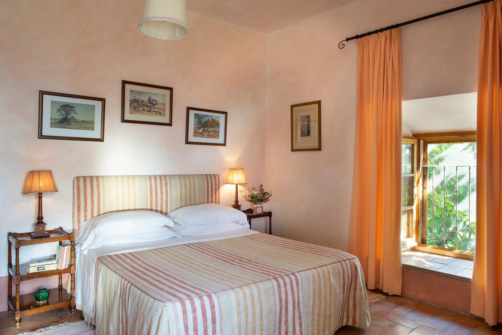 The bedroom has windows overlooking the open lawn on one side and Monte Amiata on the other.