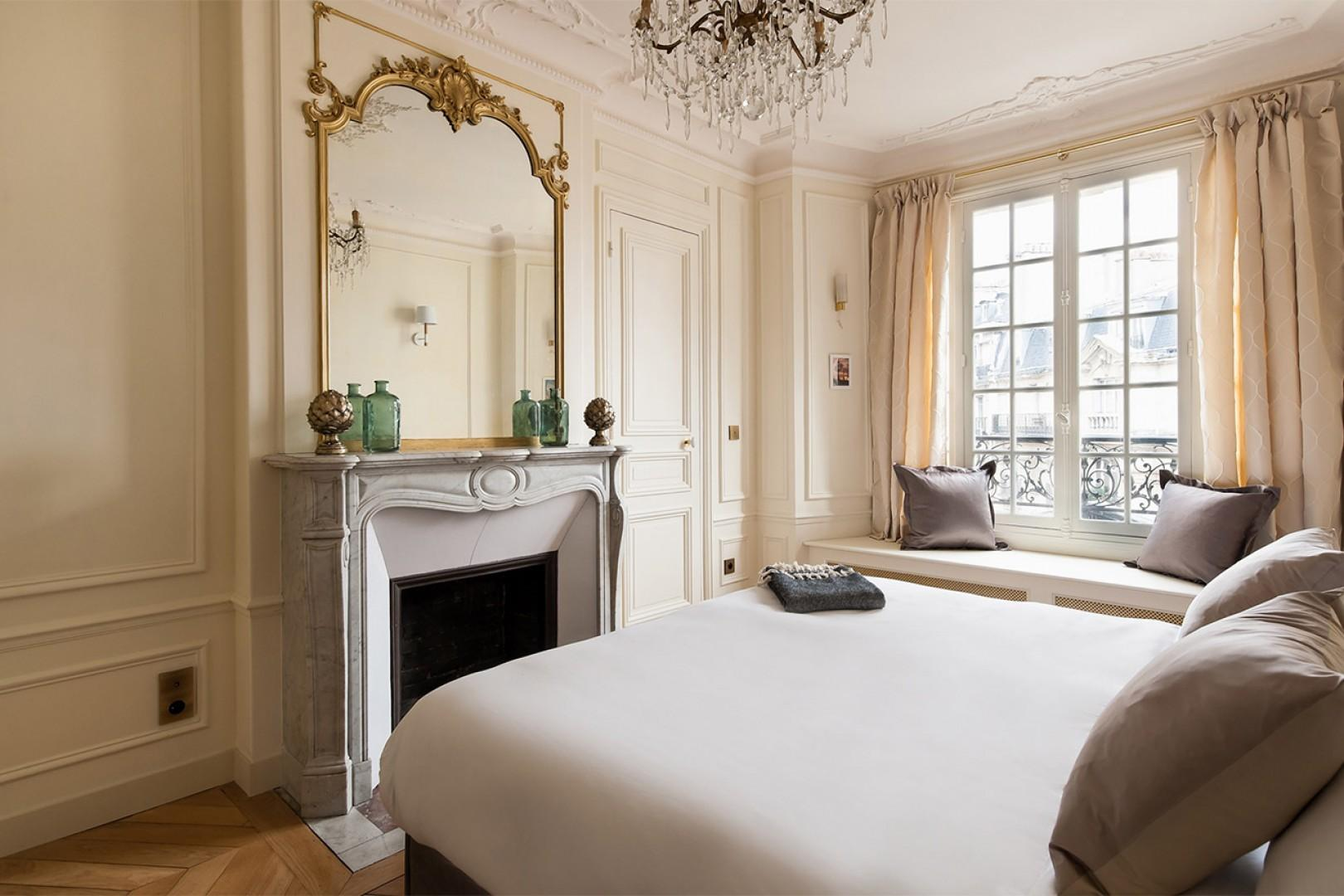 A marble fireplace and large mirror are beautiful features in bedroom 2.