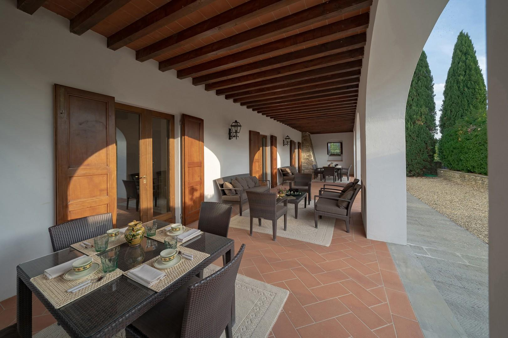 Shaded outdoor loggia with lounge chairs and outdoor dining.