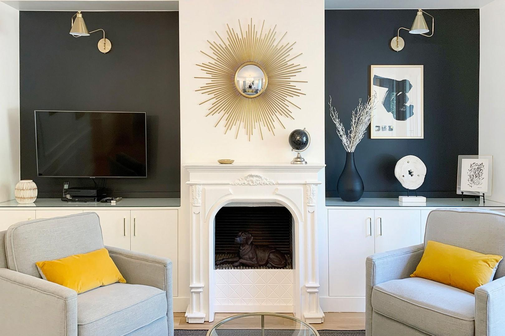 The decorative fireplace, mantle and striking sunburst mirror give the room a chic Parisian feel.