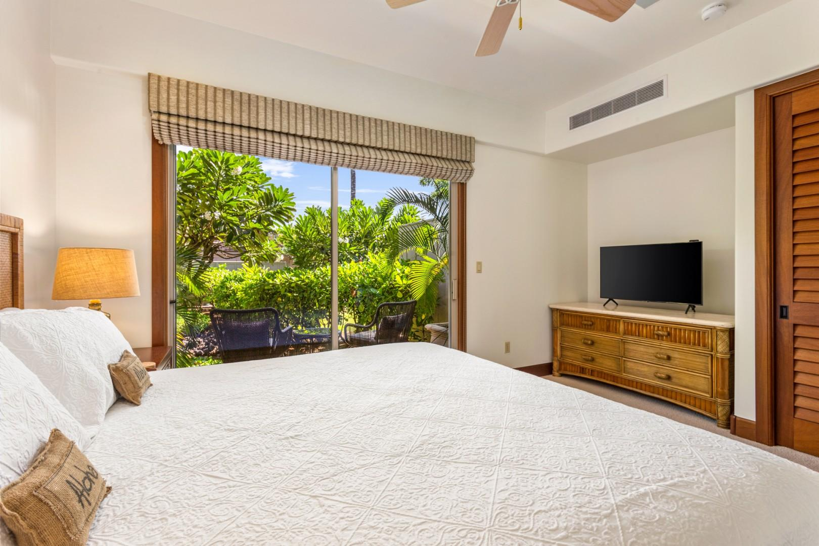 Alternate view of second bedroom showcasing private patio and flatscreen television.