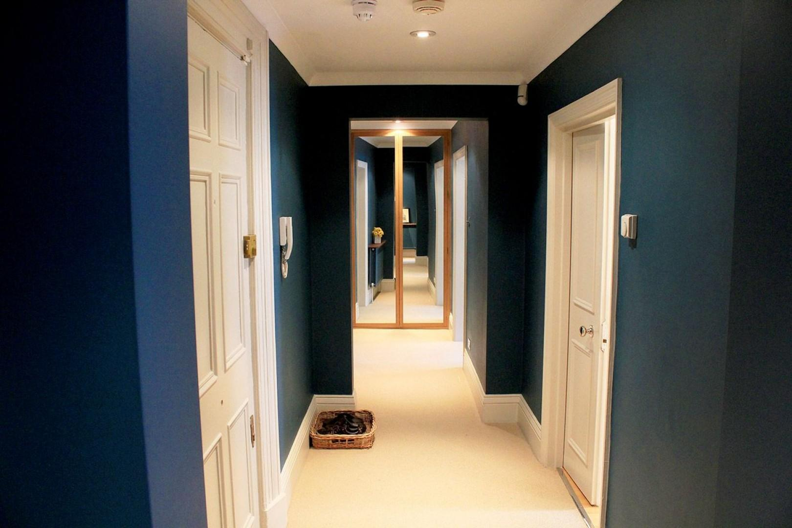 Hallway with stunning deep blue walls leads to bedrooms