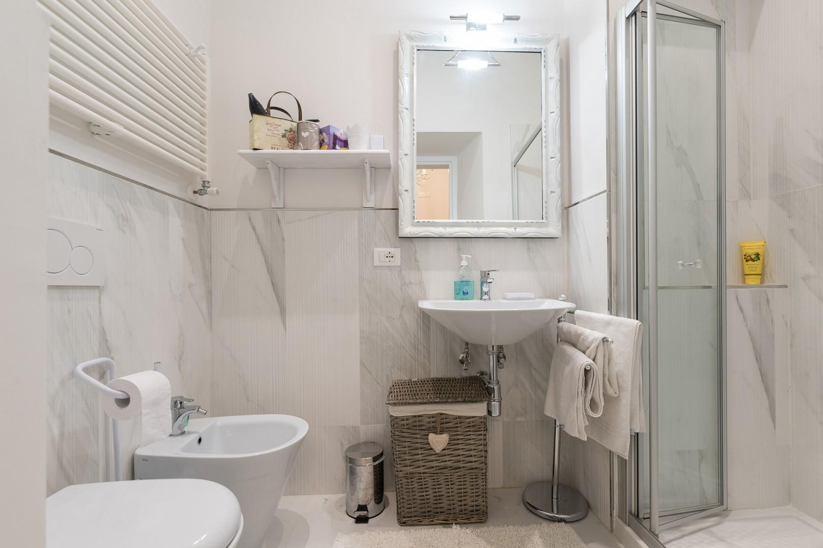 The marble-tiled bathroom is generously sized.