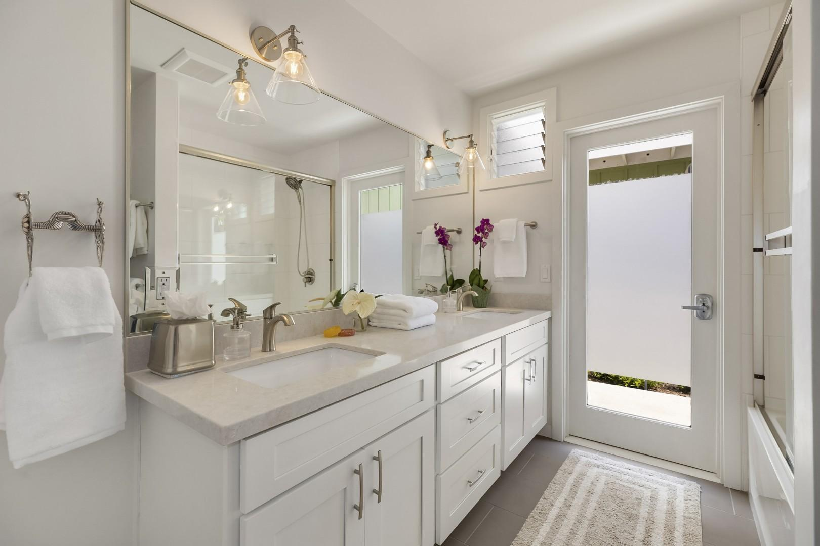 Bright Hallway Bathroom, with full size bathtub and double vanity. Opens to Outdoor Shower.