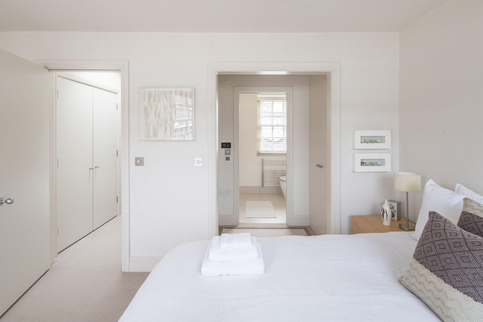 First bedroom with luxurious bed and en suite bathroom