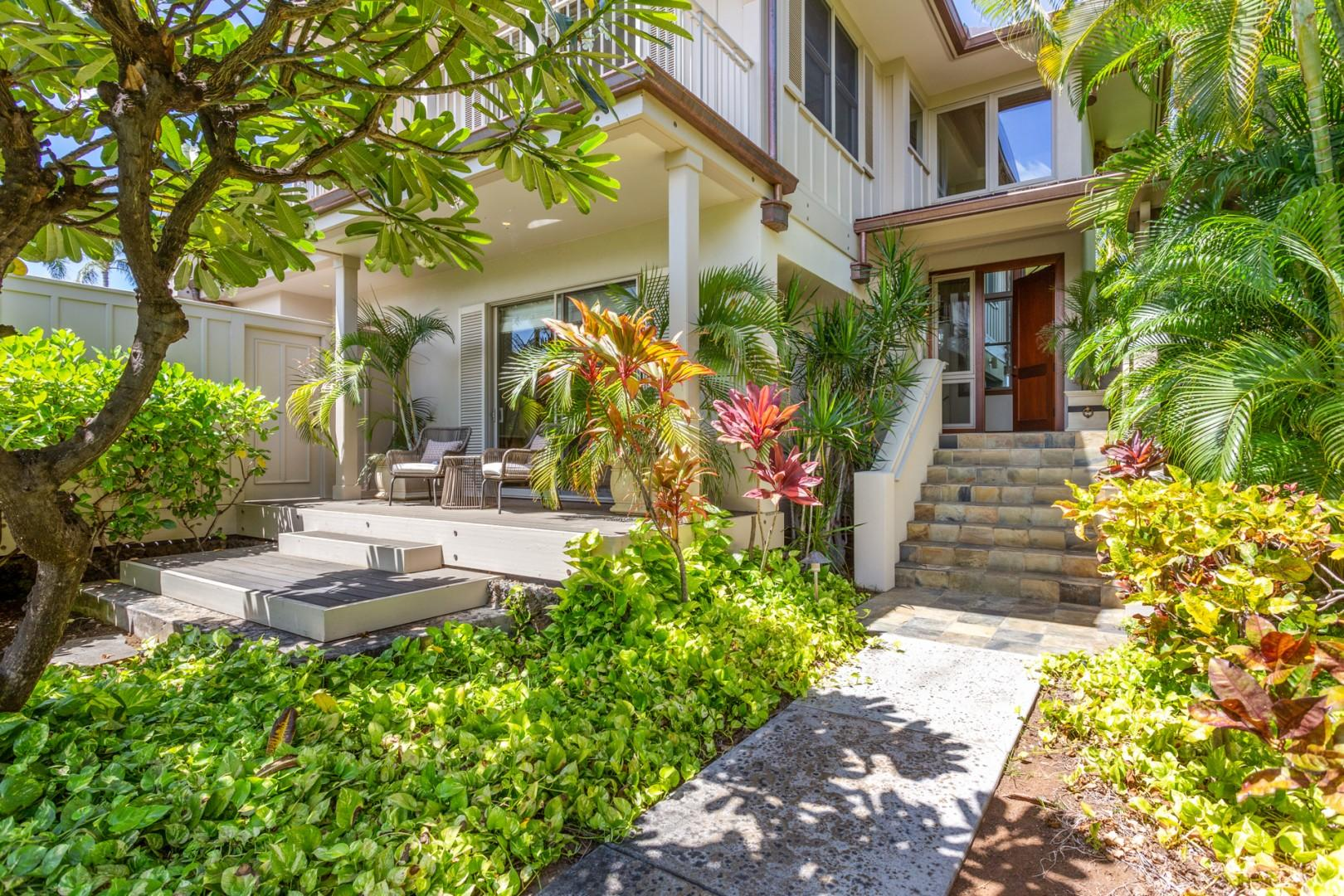 Walkway to private entrance with lush tropical landscaping.