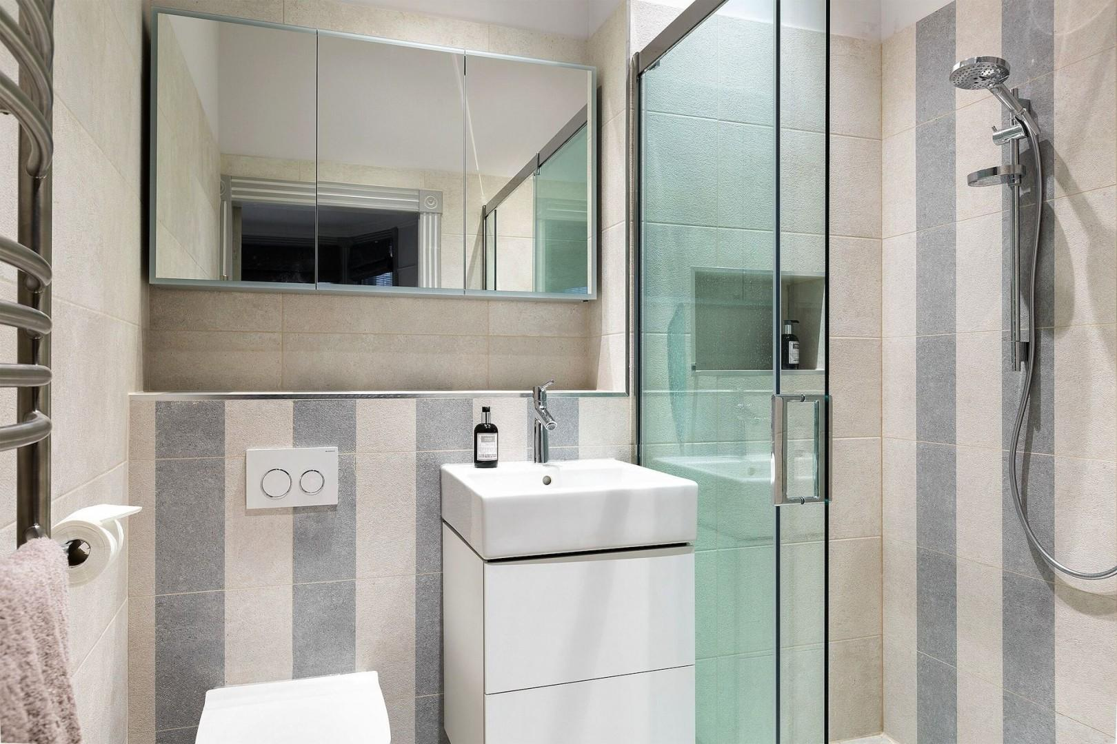 Bedroom 1 has an en suite bathroom equipped with shower, sink and toilet