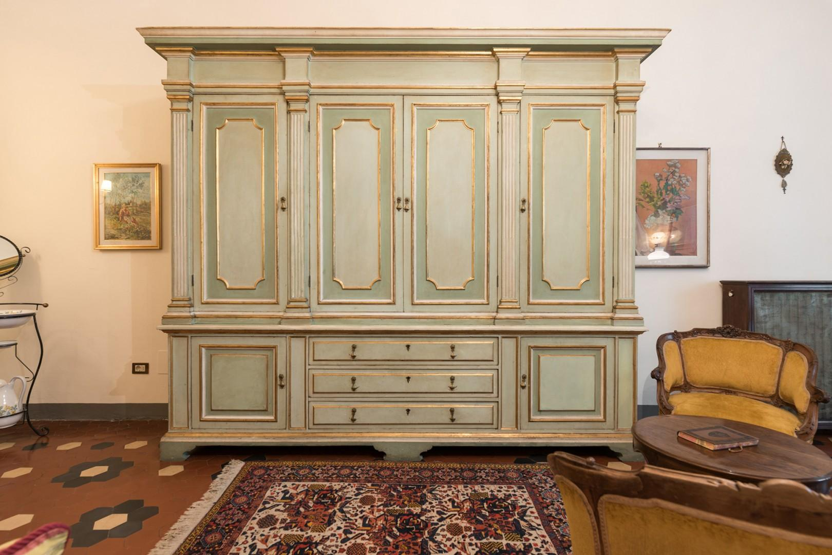 A pretty hand-painted armorie and an antique dresser provide ample clothing storage space.