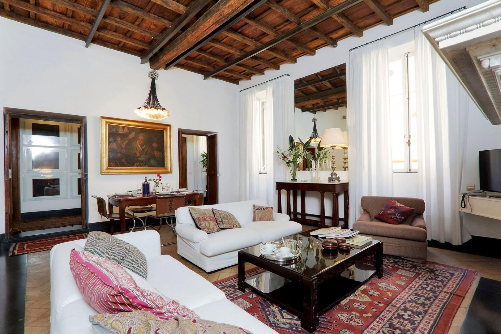 The large living room is filled with light from two large windows which overlook Via Bocca di Leone.