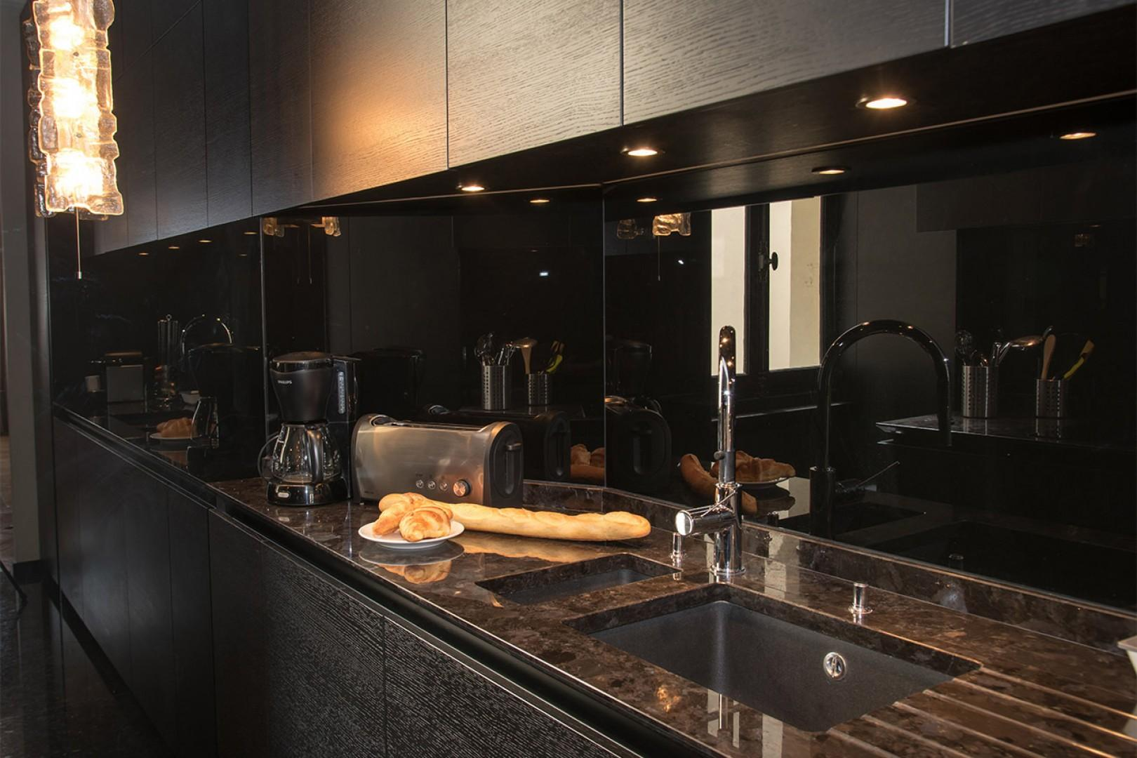 The sophisticated kitchen features high-quality modern appliances.