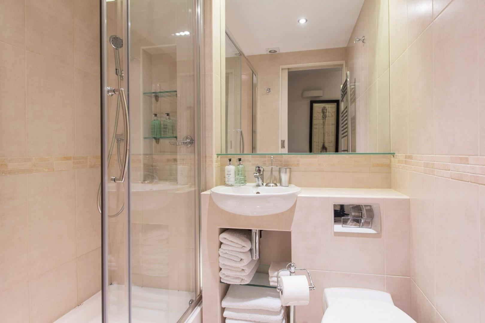 Bathroom featuring a large shower, toilet and sink
