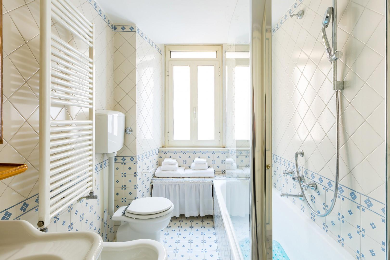 Light filled bathroom. There is a wall of closets at the opposite end of this bathroom.
