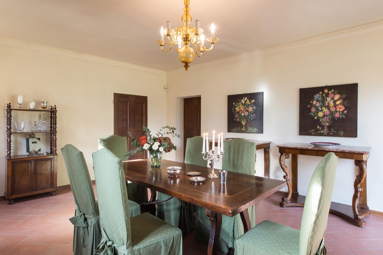 The elegant dining area opens onto the gardens and pool area through French doors.