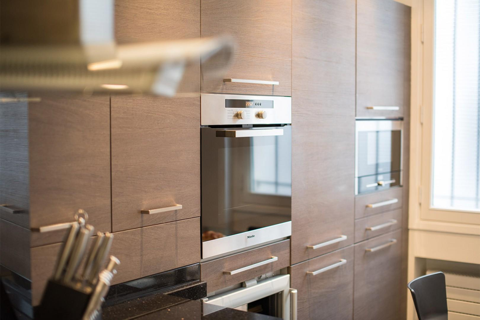 A high-end oven, microwave, fridge and wine fridge are built into the kitchen design.