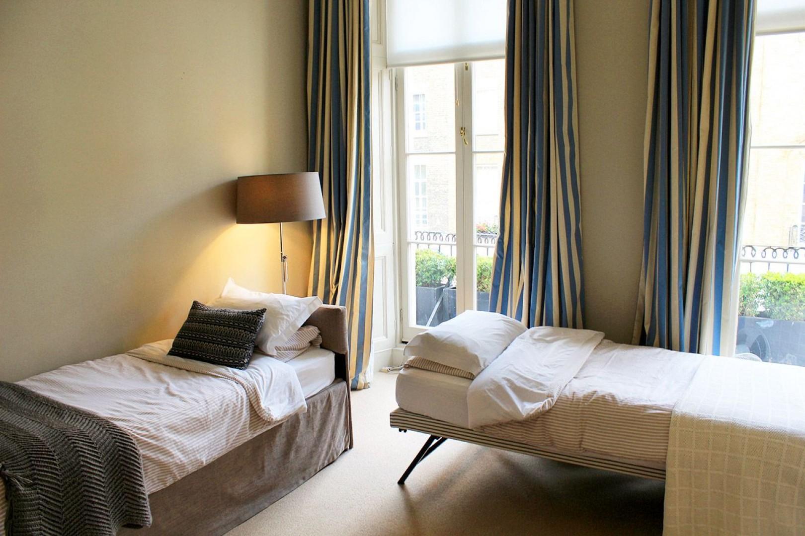 Bedroom 2 with two comfortable beds, desk and en suite bathroom